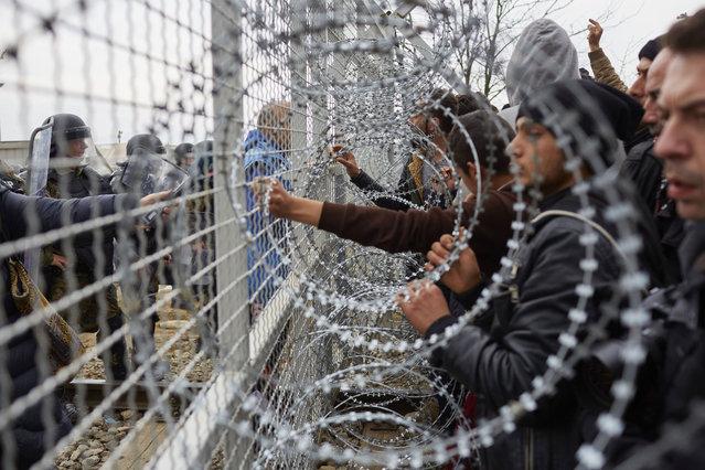 Refugees speak to the press on the Greek-Macedonia border on February 29, 2016 in Idomeni, Greece. A group of refugees forced the gate in an attempt to enter Macedonia. 7 refugees were injured during the riot. Tear gas and sound grenades were fired to clear the railway. The transit camp has become overcrowded as refugees continue to arrive from Athens and the Greek Islands. Macedonia opened its border with Greece allowing 580 refugees a day to cross into the country. (Photo by Pierre Crom/Getty Images)
