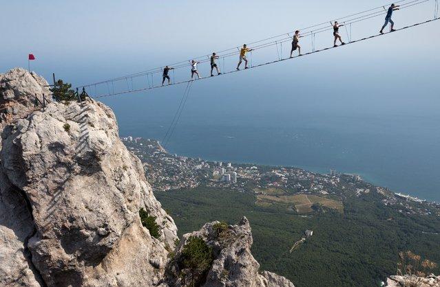 Tourists walk on the Sky Trail suspension bridge on Mount Ai Petri in southern Crimea, Russia on August 29, 2021. (Photo by Sergei Malgavko/TASS)