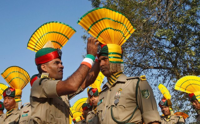 An Indian paramilitary soldier adjusts the headgear of his colleague before taking part in the Republic Day parade in Agartala, India, January 26, 2017. (Photo by Jayanta Dey/Reuters)