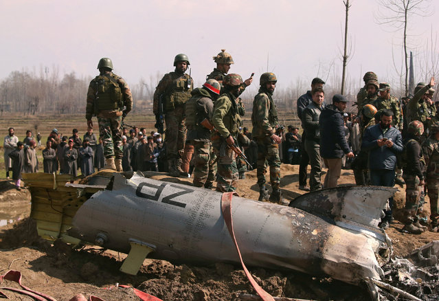 Indian soldiers stand next to the wreckage of an Indian Air Force helicopter after it crashed in Budgam district in Kashmir February 27, 2019. (Photo by Danish Ismail/Reuters)