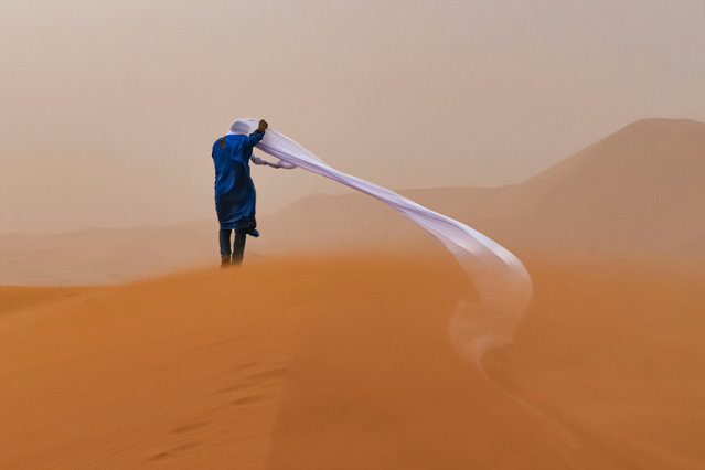 People and nature second place: Tom Overall, Australia. A guide in the Sahara desert endures a sand storm. (Photo by Tom Overall/TNC Photo Contest 2021)