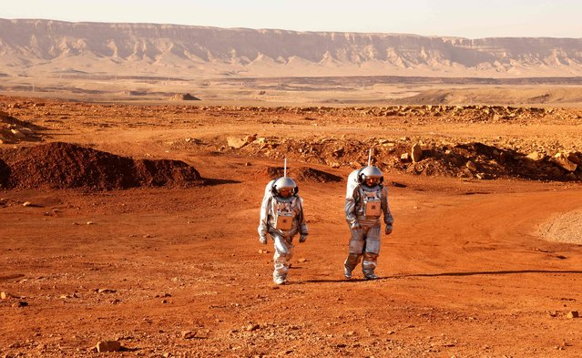 A couple of astronauts from a team from Europe and Israel walk in spacesuits during a training mission for planet Mars at a site that simulates an off-site station at the Ramon Crater in Mitzpe Ramon in Israel's southern Negev desert on October 10, 2021. Six astronauts from Portugal, Spain, Germany, the Netherlands, Austria, and Israel will be cut off from the world for a month, from October 4-31, only able leave their habitat in spacesuits as if they were on Mars. Their mission, the AMADEE-20 Mars simulation, will be carried out in a Martian terrestrial analog and directed by a dedicated Mission Support Center in Austria, to conduct experiments ahead of future human and robotic Mars exploration missions. (Photo by Jack Guez/AFP Photo)