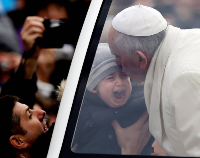 Pope Francis kisses a crying child during his tour through the crowd in St. Peter's Square, part of his weekly general audience at the Vatican, Wednesday, January 29, 2014. (Photo by Gregorio Borgia/AP Photo)