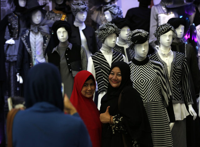 Visitors pose for a photograph next to clothing on display at the Indonesia Fashion Week in Jakarta, Indonesia March 11, 2016. (Photo by Darren Whiteside/Reuters)