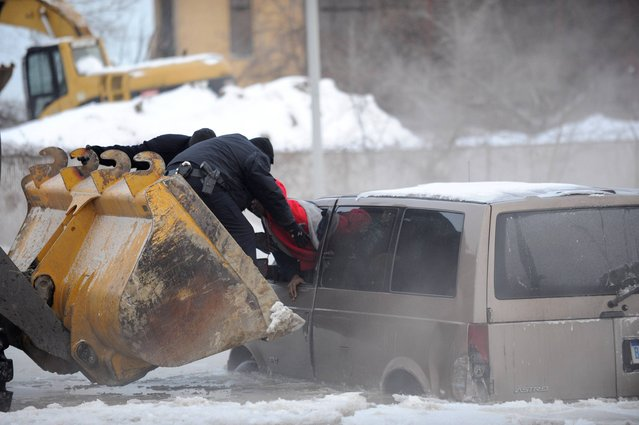 Detroit police use the scoop of a front-end loader to carry two people stranded in a minivan to safety after street flooding caused by a water main break on Friday, February 7, 2014 on Detroit's east side. Several vehicles were stuck in water and ice, prompting a rescue by police officers on construction equipment. The break was reported about 5 a.m. Friday in the area of Gratiot Avenue at Conner Street. (Photo by David Coates/AP Photo/The Detroit New)