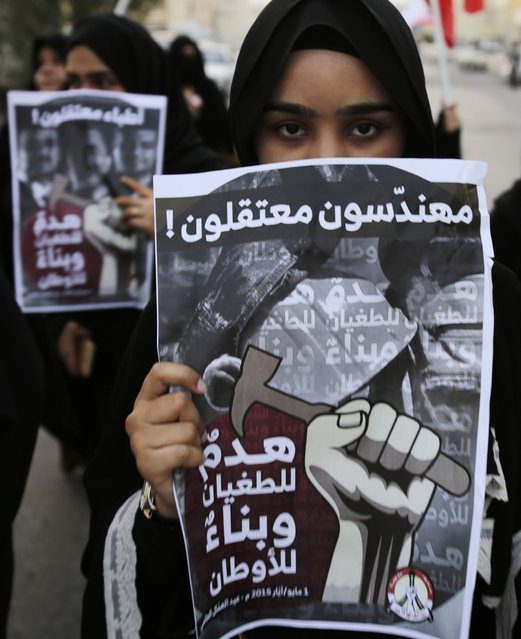 "Bahraini anti-government protesters hold up posters calling for freedom for jailed doctors, rear, and engineers, foreground, in Manama, Bahrain, Friday, May 1, 2015. The front poster reads: ""Imprisoned Engineers! Destroying tyranny and building nations"". (Photo by Hasan Jamali/AP Photo)"