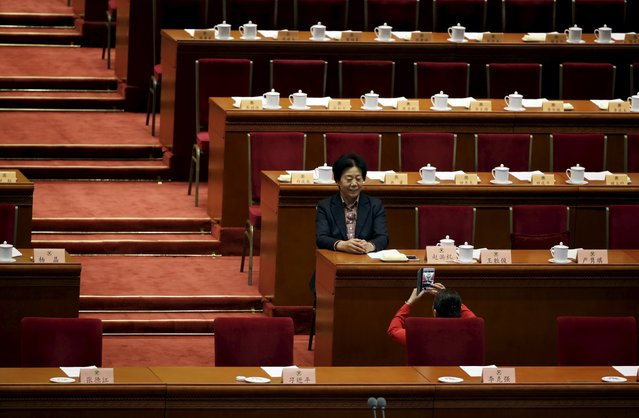 A woman poses for pictures ahead of the closing ceremony of the Chinese People's Political Consultative Conference (CPPCC) at the Great Hall of the People, in Beijing, China, March 14, 2016. (Photo by Jason Lee/Reuters)
