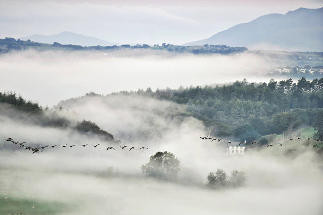 Morning mist cloaks the meandering Eden Valley in Cumbria, England this morning on September 23, 2018, where the Lakeland fells bathe in sunshine from the rising sun, the first hints of Autumn are seen above the water of the River Eamont. (Photo by Paul Kingston/North News and Pictures)