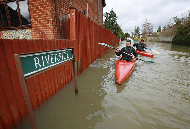 A couple of residents canoe along a road called Riverside in  flooded Wraysbury on February 11, 2014 in England. The Environment Agency has issued severe flood warnings for a number of areas on the river Thames west of London. (Photo by Peter Macdiarmid/Getty Images)