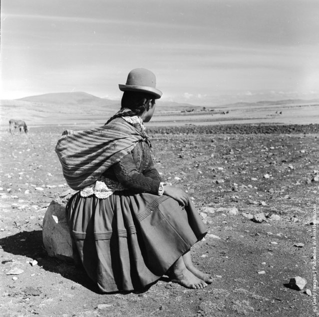 Burdened with a shawl full of her belongings, a woman stops for a rest on the road between Julaca and Puno in Peru, 1955