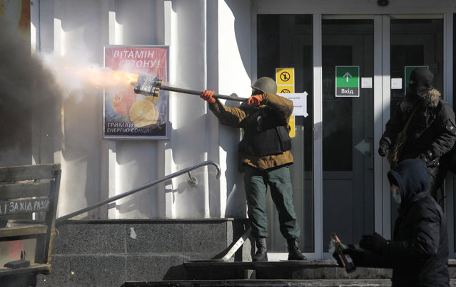 An anti-government protester fires an improvised weapon during clashes with riot police  outside Ukraine's parliament in Kiev, Ukraine, Tuesday, February 18, 2014. Thousands of anti-government protesters clashed with police in a new eruption of violence Tuesday. (Photo by Sergei Chuzavkov/AP Photo)