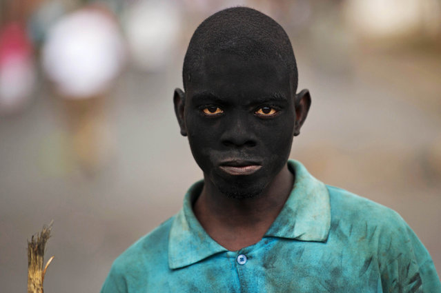A protester with his face smeared with soot from burning barricades stands in the Musaga neighbourhood of Bujumbura on May 6, 2015. Government and opposition rivals are meeting in Burundi in a bid to end deadly demonstrations against a third term bid by the president, as regional foreign ministers arrived to add pressure. (Photo by Phil Moore/AFP Photo)