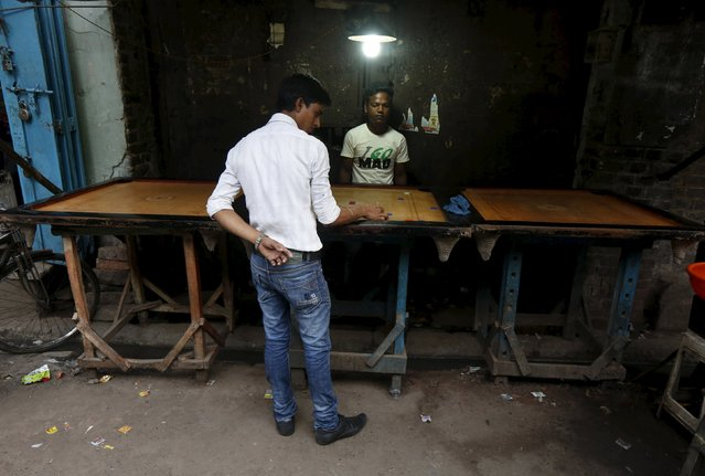 Mohammad Kausar, 24, and Mohammad Aslam, 25, play carrom at the roadside in a market area in Kolkata, India, March 12, 2016. They said that Kolkata is a good place for people of all religions to live, work, play and eat together. Some people in Kolkata earn a living by selling second-hand clothes, driving rickshaws or in the city's food markets. Those too poor to afford a home of their own sleep where they work, helping people who moved to the city to find work to send money back home. Outside working hours residents of the city formerly called Calcutta might enjoy a game of chess or carrom, while children play soccer with friends. (Photo by Rupak De Chowdhuri/Reuters)
