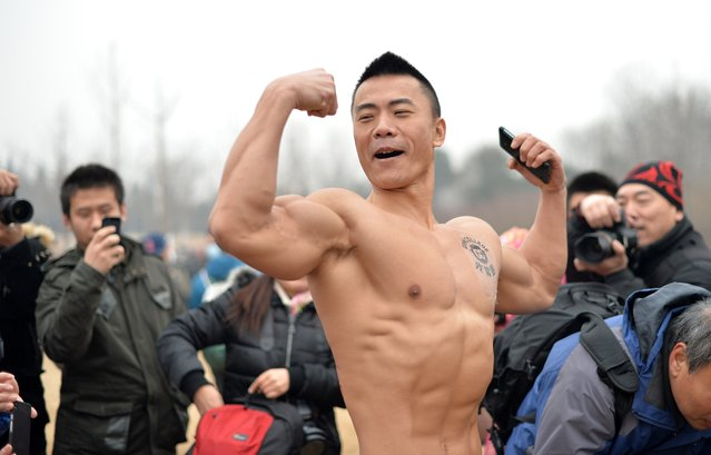 This picture taken on February 23, 2014 shows a participant showing his muscles as he takes part in the annual 3.5 km Undie Run held in the Olympic Forest Park smog-covered Beijing. (Photo by AFP Photo/STR)