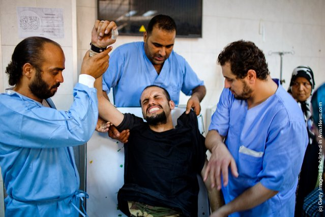 A Libyan Rebel fighter grimaces as he receives medical attention after being brought in with a gun wound to his torso at the Tripoli Central Hospital