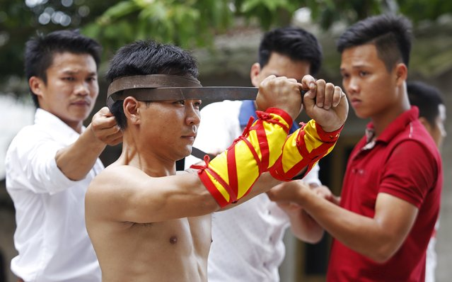 Dang Tien Duy (front), 28, bends a metal bar around his head as he performs during a showcase of the traditional Thien Mon Dao kung fu at Du Xa Thuong village, southeast of Hanoi, Vietnam May 10, 2015. (Photo by Reuters/Kham)