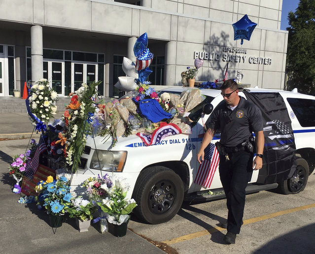 In this photo provided by WLOX, an unidentified Biloxi, Miss., police officer walks away after placing an angel statuette on Biloxi Police Officer Robert McKeithen's official vehicle, Monday, May, 6, 2019. McKeithen was shot in an ambush in front of the police station Sunday night. (Photo by John Fitzhugh/WLOX via AP Photo)
