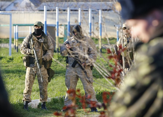 Armed men, believed to be Russian servicemen, stand guard at a military airbase in the Crimean town of Belbek near Sevastopol March 22, 2014. (Photo by Shamil Zhumatov/Reuters)