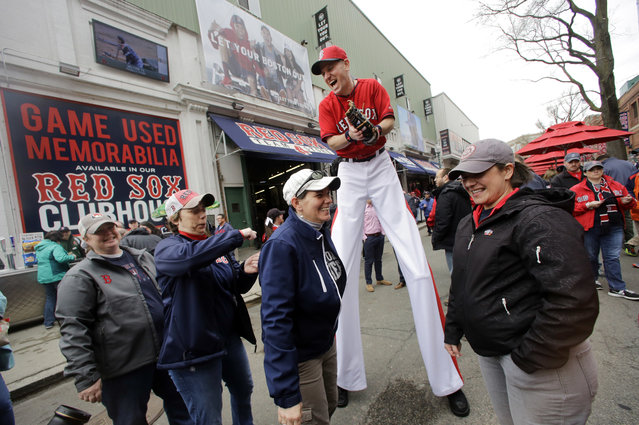 """""""Big League Brian"""" on stilts laughs with fans on Yawkey Way before the home opener baseball game between the Boston Red Sox and the Baltimore Orioles at Fenway Park, Monday, April 11, 2016, in Boston. (Photo by Elise Amendola/AP Photo)"""