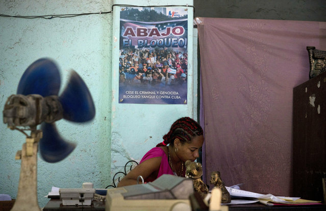 "A woman works in a government office where a sign hangs on the wall that reads in Spanish: ""Down with the embargo"" in Havana, Cuba, Wednesday, April 17, 2019. The Trump administration on Wednesday intensified its crackdown on Cuba, Nicaragua and Venezuela, rolling back Obama administration policy and announcing new restrictions and sanctions against the three countries whose leaders national security adviser John Bolton dubbed the ""three stooges of socialism"". (Photo by Ramon Espinosa/AP Photo)"