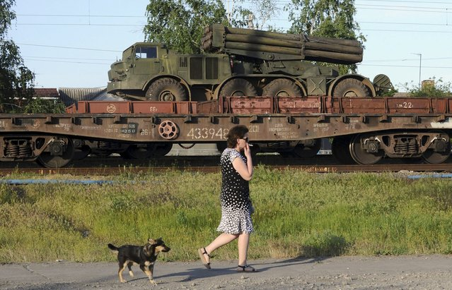 A multiple launch rocket system is seen on a freight train platform as a woman and a dog pass by in the Russian southern town of Matveev Kurgan, near the Russian-Ukrainian border in Rostov region, Russia, May 23, 2015. A train with about 20 multiple launch rocket systems and dozens of military trucks, accompanied by Russian servicemen, arrived on May 23 in Matveev Kurgan, according to a Reuters journalist. (Photo by Reuters/Stringer)