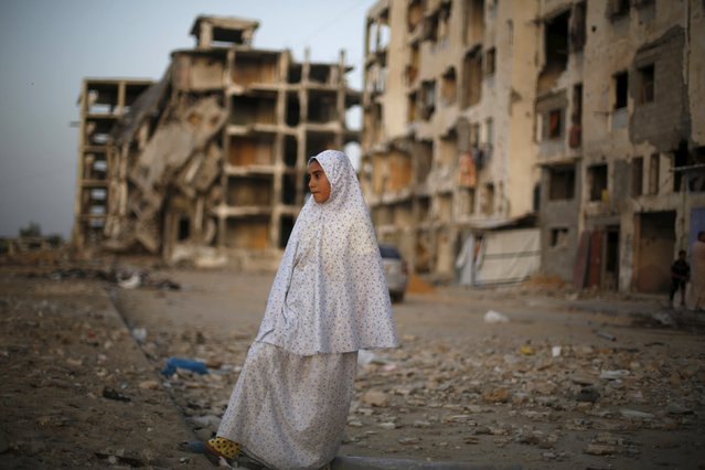 A Palestinian girl stands near residential buildings that witnesses said were heavily damaged by Israeli shelling during a 50-day war last summer, in Beit Lahiya town in the northern Gaza Strip May 25, 2015. (Photo by Suhaib Salem/Reuters)