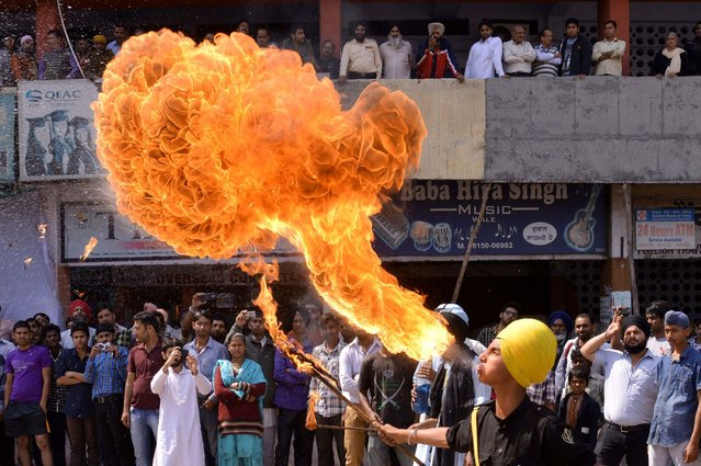 Indian Sikh youths perform fire-breathing as they demonstrate Gatka martial arts skills while welcoming unseen Bharatiya Janata Party (BJP) senior leader and candidate for Amritsar's parliamentary seat Arun Jaitley to an event in Amritsar on March 18, 2014. (Photo by Narinder Nanu/AFP Photo)