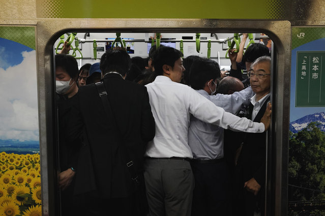 In this Tuesday, May 21, 2019, photo, commuters stand in a packed Yamanote Line train at Shinjuku Station in Tokyo. Trains are always packed during morning and evening rush hours as they are notoriously known. It's so densely packed that passengers don't even have to grab a handrail to stand upright despite swaying. There are shoves from commuters who can't afford to wait another few minutes for a next train, but no one growls in irritation. It's usually forgiven with just a little nod, a gesture of apology. (Photo by Jae C. Hong/AP Photo)
