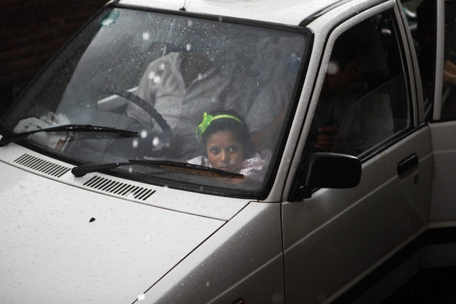 In this August 19, 2015 photo, Nirmala Pariyar, 8, looks out a car window after her best friend Khendo, also 8, was dropped off at a relative's house. Both girls had grown inseparable after each lost a leg in the massive 2015 Nepal earthquake and spent the following months in recovery together. (Photo by Niranjan Shrestha/AP Photo)