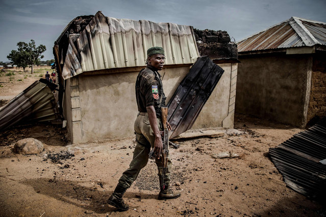 A Nigerian Police Officer patrols an area of destroyed and burned houses after a recent Fulani attack in the Adara farmers' village of Angwan Aku, Kaduna State, Nigeria, on April 14, 2019. The ongoing strife between Muslim herders and Christian farmers, which claimed nearly 2,000 lives in 2018 and displaced hundreds of thousands of others, is a divisive issue for Nigeria and some other countries in West Africa. (Photo by Luis Tato/AFP Photo)