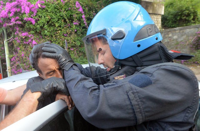 Italian police officers push a migrant inside a car in Ventimiglia, at the Italian-French border Tuesday, June 16, 2015. Police at Italy's Mediterranean border with France have forcibly removed some of the African migrants who have been camping out for days in hopes of continuing their journeys farther north. The migrants, mostly from Sudan and Eritrea, have been camped out for five days after French border police refused to let them cross. (Luca Zennaro/ANSA via AP)
