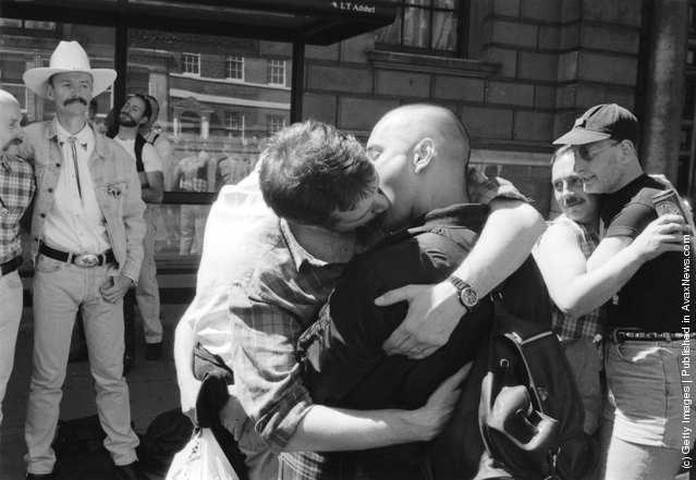 Male revellers hugging and kissing during the Gay Pride parade in London