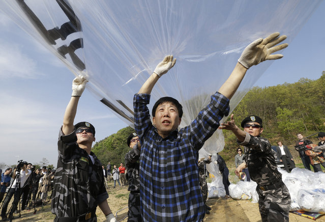 "North Korean defectors prepare to release balloons carrying leaflets condemning North Korean leader Kim Jong Un during a rally against North Korea in Paju, near the border with North Korea, South Korea, Friday, April 29, 2016. North Korea on Friday accused U.S. soldiers of trying to provoke its frontline troops with ""disgusting"" acts and encouraging South Korean soldiers to aim their guns at the North. (Photo by Ahn Young-joon/AP Photo)"