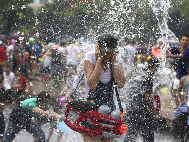 A participant dodges in the annual water-splashing festival to mark the New Year of the Dai minority in Xishuangbanna, Yunnan province. (Photo by Wong Campion/Reuters)