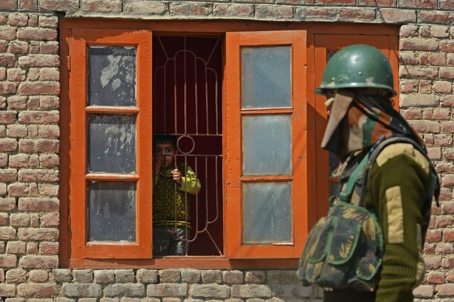 A Kashmiri child looks out a window as an Indian paramilitary trooper walks past near the vicinity of a gunfight between suspected militants and Indian troops in the outskirts of Srinagar on April 14, 2014. Two militants are holed up inside a house on the outskirts of the city as security forces tightened their cordon in Ahmadnagar locality of Srinagar, police said. (Photo by Tauseef Mustafa/AFP Photo)
