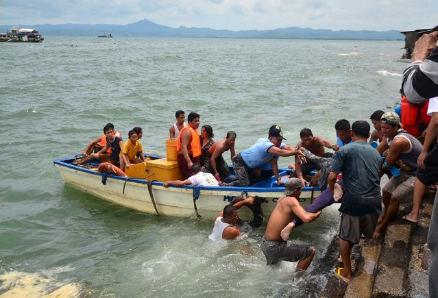 A body is carried by rescuers during a search and rescue operation following a ferry capsize in Ormoc city, central Philippines July 2, 2015. (Photo by Reuters/Stringer)