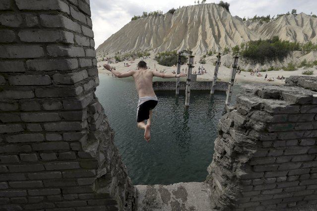 A man jumps into water from the roof of the abandoned Soviet time prison in Rummu quarry, Estonia, during hot weather July 4, 2015. During the Soviet time, Rummu quarry was used as a mining site for Vasalemma marble and most of the workforce came from among the detainees of Murru prison. When the prison closed after 1991, pumps that once kept the quarry and the prison dry were shut down, causing water to fill the quarry. (Photo by Ints Kalnins/Reuters)