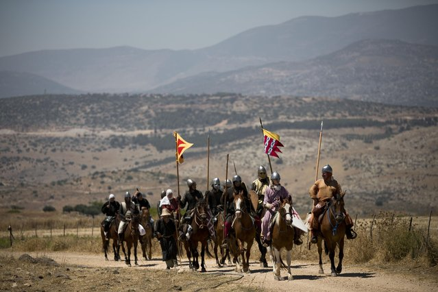 In this Saturday, July 4, 2015 photo, Israeli and Russian members of knight clubs, ride their horses on their way to the reenactment of the Battle of Hattin in Horns of Hattin, northern Israel. (Photo by Oded Balilty/AP Photo)
