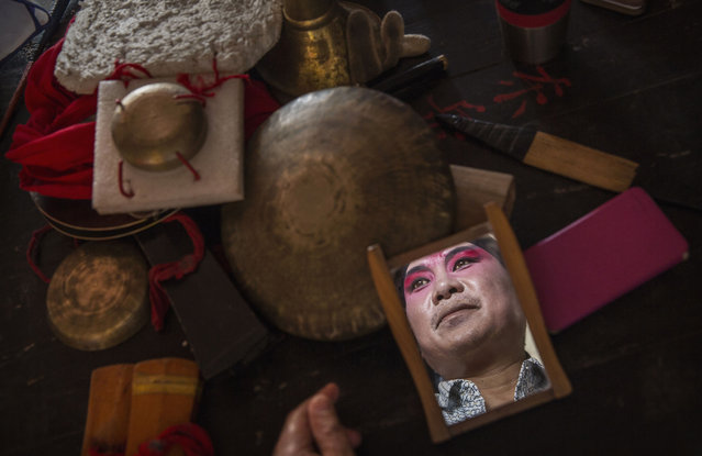 Sichuan Opera performer Wu Dezhi, 51 years, of the Jinyuan Opera Company prepares during the group's performance at the Dongyue Temple on May 2, 2016 in Cangshan, Sichuan province, China. (Photo by Kevin Frayer/Getty Images)