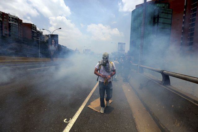 A demonstrator walks in the middle of a cloud of tear gas fired by the Bolivarian National Guard during a protest in Caracas, Venezuela, Monday, April 10, 2017. (Photo by Fernando Llano/AP Photo)