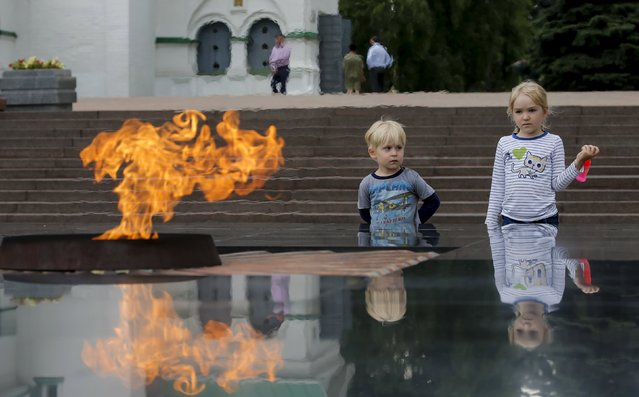 Children stand next to the Eternal Flame memorial in the town of Nizhny Novgorod, Russia, July 10, 2015. (Photo by Maxim Shemetov/Reuters)