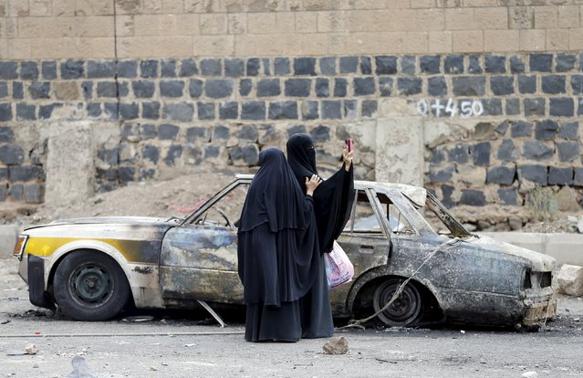 A woman takes photos with her mobile phone at the site of a Saudi-led air strike in Yemen's capital Sanaa July 14, 2015. A Saudi-led coalition of Arab states has been bombing the Iranian-allied Houthi rebel movement and army forces loyal to former Yemeni president Ali Abdullah Saleh since late March in a bid to restore exiled President Abd-Rabbu Mansour Hadi to power. (Photo by Khaled Abdullah/Reuters)