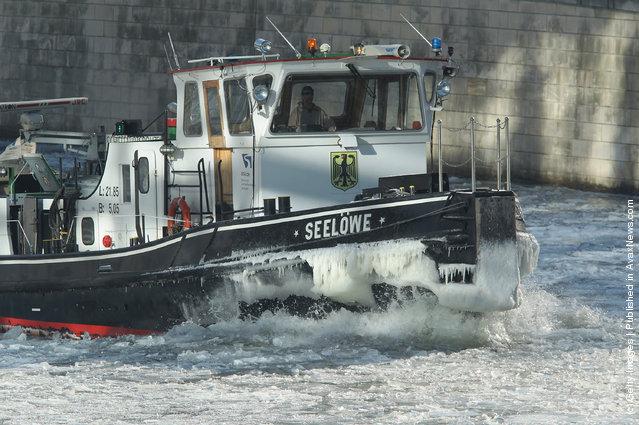 The icebreaker 'Seeloewe' (Sea Lion) makes its way through ice on the Spree river