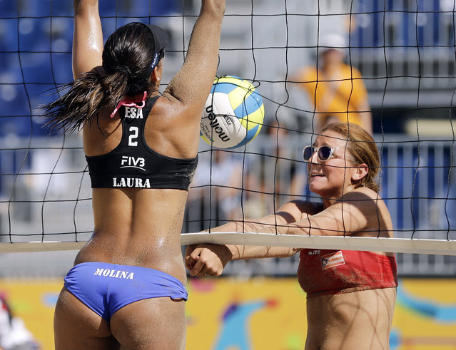Eva Torruella, right, of Puerto Rico, hits the ball into the net as Laura Molina, left, of El Salvador, reaches to block the shot during a beach volleyball game at the Pan Am Games Monday, July 20, 2015, in Toronto. El Salvador won 2-1. (Photo by Mark Humphrey/AP Photo)