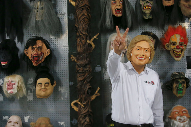 The manager of Jinhua Partytime Latex Art and Crafts Factory wears a mask of U.S. Democratic presidential candidate Hillary Clinton as he poses and gestures a victory sign while showing products to reporters at his factory's showroom in Jinhua, Zhejiang Province, China, May 25, 2016. (Photo by Aly Song/Reuters)