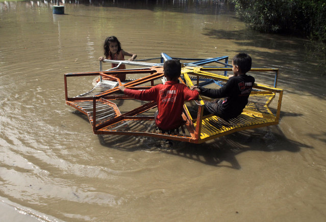 Pakistani children take a ride on a roundabout at a flooded park caused by heavy rains in Lahore, Pakistan, Tuesday, July 21, 2015. A Pakistani local government spokesman said this week's flash floods triggered by monsoon rains in the country's north have killed at least two people and damaged several homes, roads and bridges. (Photo by K. M. Chaudary/AP Photo)