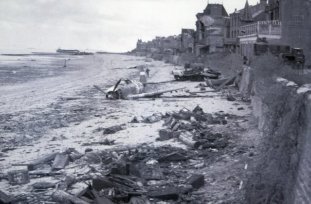 A crashed U.S. fighter plane is seen on the waterfront some time after Canadian forces came ashore on a Juno Beach D-Day landing zone in Saint-Aubin-sur-Mer, France, in June 1944. British and Canadian troops battled reinforced German troops holding the area around Caen for about two months following the D-Day landings in Normandy in 1944. REUTERS/National Archives of Canada