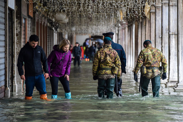 """People (L), a policeman (Rear) and military men walk across a flooded arcade on November 24, 2019 in Venice during a high tide """"Acqua Alta"""" meteorological phenomenon with a high of 140 cm expected. Flood-hit Venice was bracing for another, though smaller, high tide on November 24, after Italy declared on November 15 a state of emergency for the UNESCO city where perilous deluges have caused millions of euros worth of damage. (Photo by Miguel Medina/AFP Photo)"""