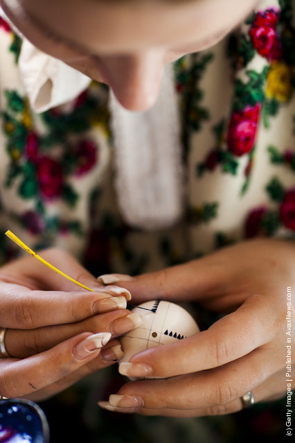 Melanie Baier from the village Obergurig wearing a traditional Lusatian sorbian folk dress, paints an Easter egg in traditional Sorbian motives at the annual Easter egg market