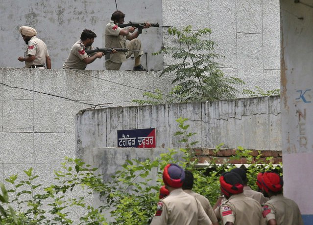 Indian policemen take their positions as their colleagues watch next to a police station during a gunfight at Dinanagar town in Gurdaspur district of Punjab, India, July 27, 2015. (Photo by Munish Sharma/Reuters)